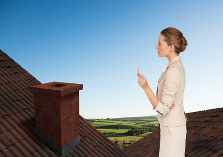 Digital composite of Businesswoman standing on Roofs with chimney and green country landscape