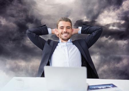 暗い空の雲の下のラップトップ上の実業家のデジタル合成