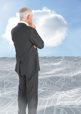 Digital composite of Businessman looking over sea of documents with cloud