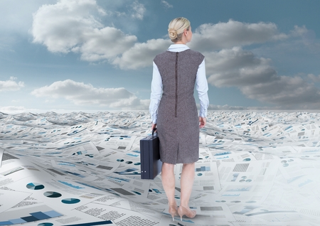 Digital composite of Businesswoman holding briefcase in sea of documents under sky clouds Stock Photo