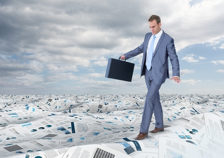 Digital composite of Businessman holding briefcase balancing in sea of documents under sky clouds