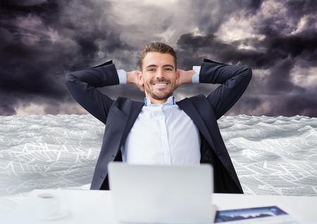 Digital composite of Businessman on laptop in sea of documents under dark sky clouds 免版税图像