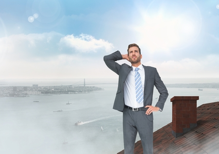 Digital composite of Businessman standing on Roof with chimney and city sea port Stock Photo