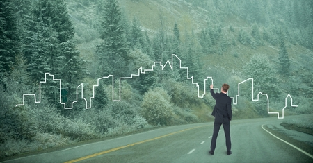Digital composite of Business man drawing a cityon the road