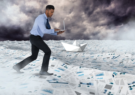 Digital composite of Businessman on laptop in sea of documents under sky clouds with paper boats