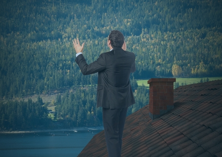 Digital composite of Businessman standing on Roof with chimney and forest mountain