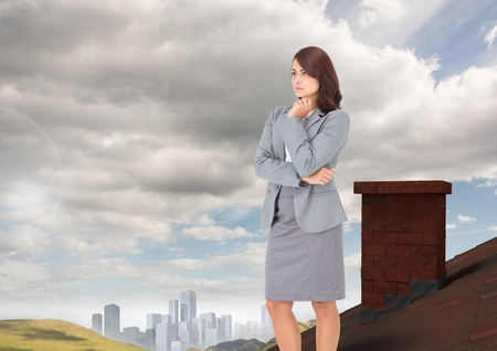 Digital composite of Businesswoman standing on Roof with chimney in country with city in distance