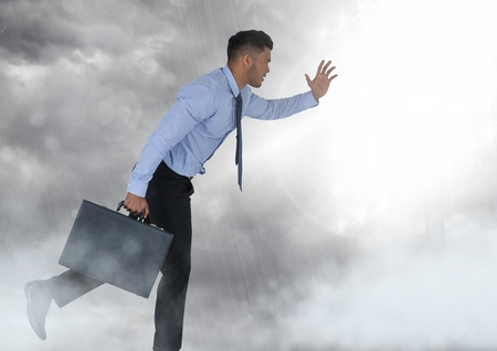 Digital composite of Businessman holding briefcase in grey sky