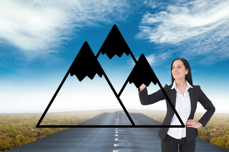 Digital composite of Business woman drawing mountains on the road
