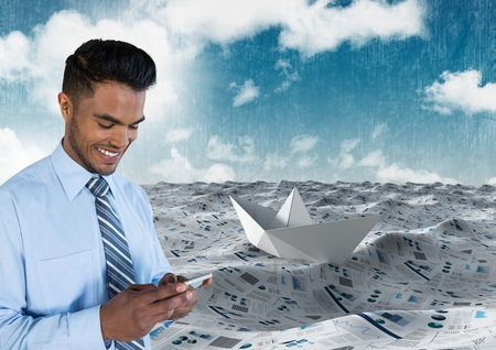 Digital composite of Businessman on phone in sea of documents under sky clouds