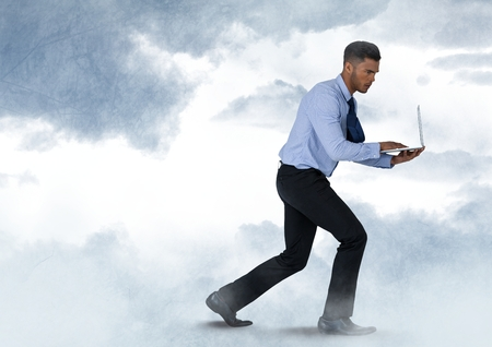 Digital composite of Businessman walking with laptop in cloudy sky