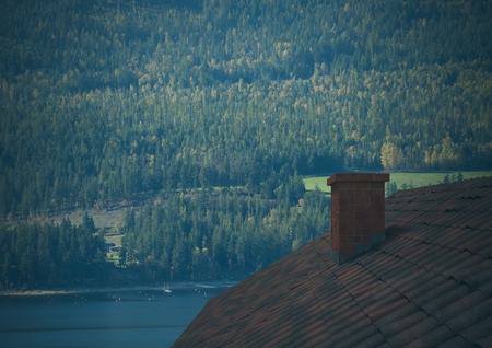 Digital composite of Roof with chimney and forest mountain