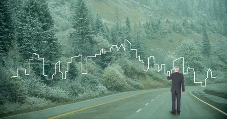 Digital composite of Business man drawing a city  on the road