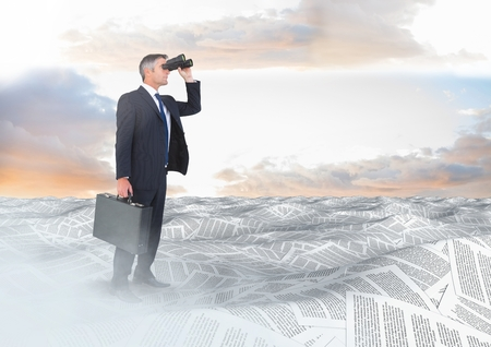 glorious: Digital composite of Businessman with binoculars and briefcase in sea of documents under sky clouds