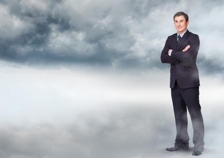 Digital composite of Businessman folding arms in cloudy sky Stock Photo