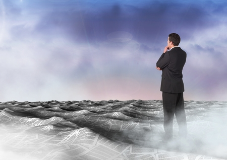 man looking out: Digital composite of Businessman in sea of documents under sky clouds Stock Photo