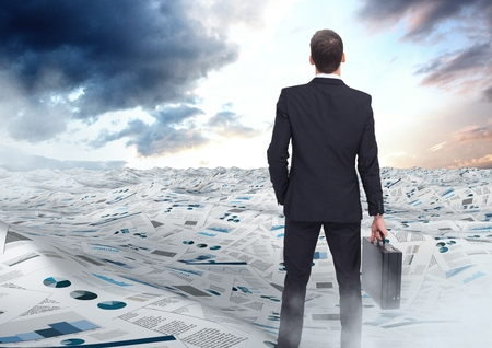 Digital composite of Businessman holding briefcase in sea of documents under sky clouds opening