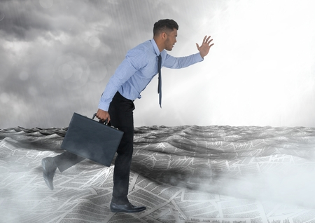 Digital composite of Businessman running with briefcase in sea of documents under sky clouds