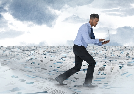 Digital composite of Businessman on laptop in sea of documents under sky clouds Stock fotó