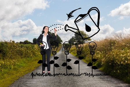 Digital composite of Business woman drawing bulb plants on the road Stock Photo