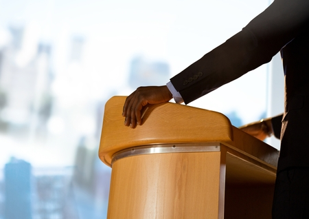 Digital composite of Businessman on podium speaking at conference with windows