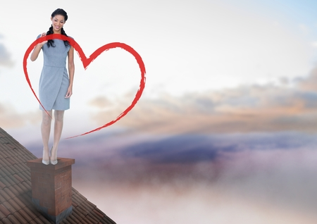 Digital composite of Heart drawing and Businesswoman standing on Roof with chimney and colorful sky Stock Photo
