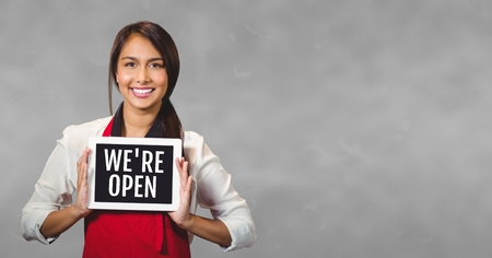 Digital composite of Business woman holding a tablet with we are open text