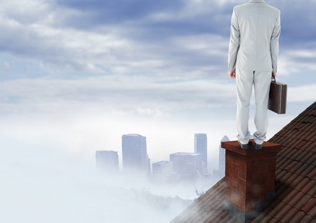 Digital composite of Businessman on roof chimney with city in distance