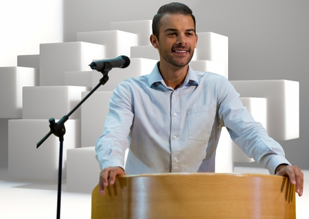 Digital composite of Businessman on podium speaking at conference with cubes