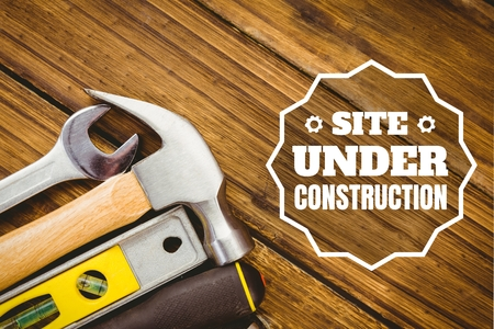 Digital composite of Website under construction text against tools photo Stock Photo