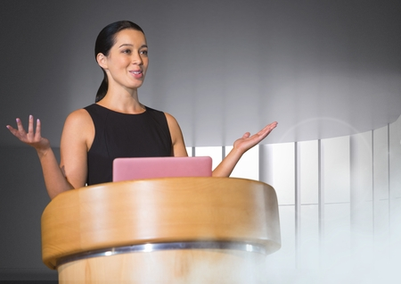 Digital composite of Businesswoman on podium speaking at conference with windows Stock Photo
