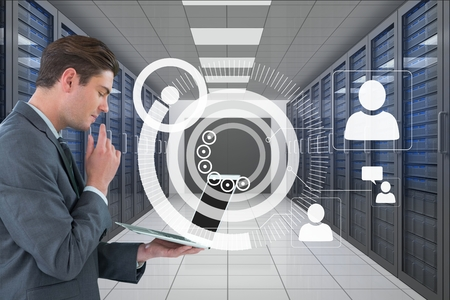 Digital composite of Business man holding a computer and graphics in server room