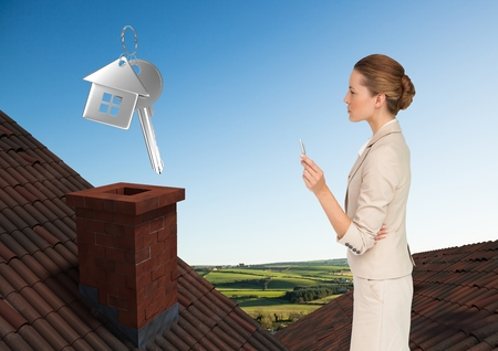 Digital composite of 3D House keys and Businesswoman standing on Roofs with chimney and green country landscape
