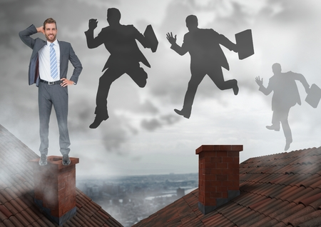 Digital composite of Businessman standing on Roofs and businessmen silhouettes jumping with chimney and cloudy city