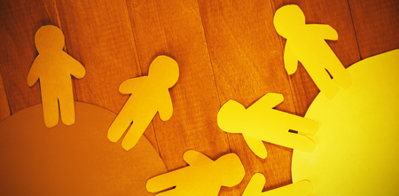 High angle view of blue and yellow paper cut out figures on wooden table