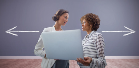 Portrait of businesswomen posing with laptop against room with wooden floor