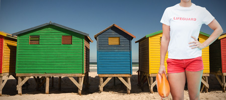 Mid section of female lifeguard holding rescue buoy against colorful huts on sand at beach