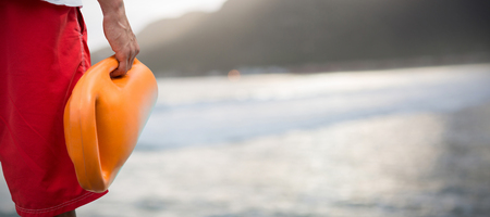 Cropped image of man holding rescue buoy against mountain against sky at beach Stock Photo