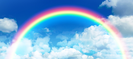 Composite image of rainbow against idyllic view of clouds against sky