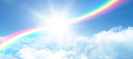 Illustration image of rainbow against view of overcast against blue sky Stock Photo