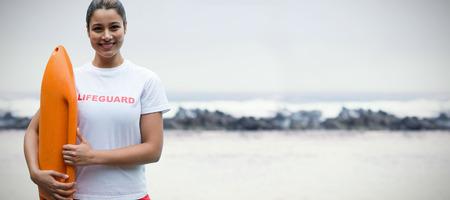 波のビューに対して救助ブイを保持している女性のライフガードの肖像画