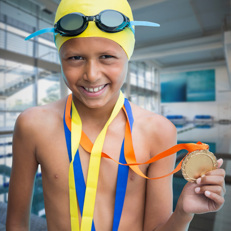 Portrait of smiling boy showing medal against empty swimming pool with large windows Stock Photo