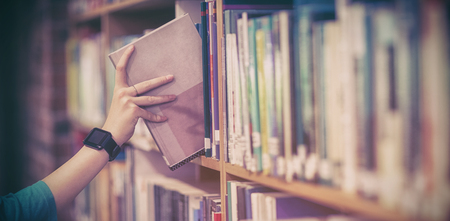 Students hand with smartwatch picking book from bookshelf at university Foto de archivo