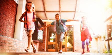 Kids running in school corridor on sunny day