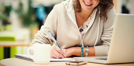 Cheerful female student doing homework by laptop at cafeteria table