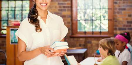 Portrait of pretty teacher holding books while standing at library Stock Photo