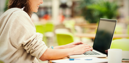Side view of a female student using laptop at cafeteria table