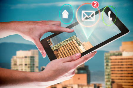 Hands using digital tablet against white background against buildings in city against blue sky