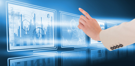 Businesswoman pointing against computer graphic image of business graphs in 3d