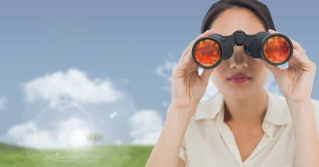 Digital composite of Businesswoman in nature field with binoculars